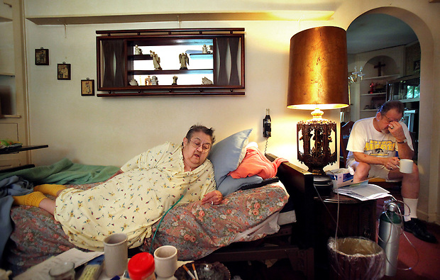 """Helen Hewitt, 72, lies on a bed in the living room of her Des Moines home on Friday with her nephew, Paul Anderson, far right.  She has been unable to pay her utilities and mortgage and is facing a forced move to a nursing home.  She suffers from chronic obstructive pulmonary disease (COPD) and other ailments, and wants very much to stay home and die in her own house. """"My guts just roll,"""" she says of her mounting debt and the likelihood of being forced to move to a nursing home."""