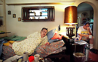 "Helen Hewitt, 72, lies on a bed in the living room of her Des Moines home on Friday with her nephew, Paul Anderson, far right.  She has been unable to pay her utilities and mortgage and is facing a forced move to a nursing home.  She suffers from chronic obstructive pulmonary disease (COPD) and other ailments, and wants very much to stay home and die in her own house. ""My guts just roll,"" she says of her mounting debt and the likelihood of being forced to move to a nursing home."