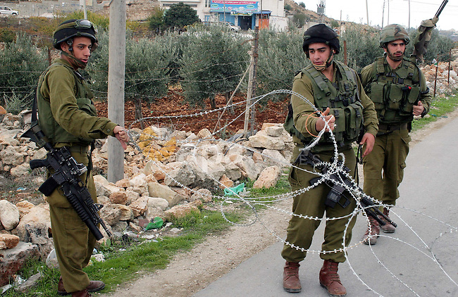 Israeli soldiers and Israeli border policemen stand guard behind razor-wire as Palestinian , Israeli activists and International activists during a rally against Israel's separation barrier in the West Bank village of al-Masarah near Bethlehem December 04, 2009. Photo by Najeh Hashlamoun