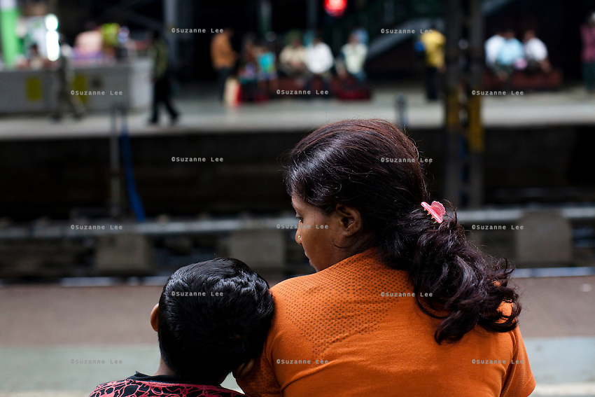 Razia Shabnam (in orange) waits for her colleagues to pick her up at the train station with her son Saihaan, to referee an all-India invitational boxing competition in the neighbouring town of Burnpur, Calcutta, West Bengal, India. Razia Shabnam, 28, was one of the first women boxers in Kolkata. She was also the first woman in her community to go to college. She is now a coach and one of only three international female boxing referees in India. Photo by Suzanne Lee for Panos London