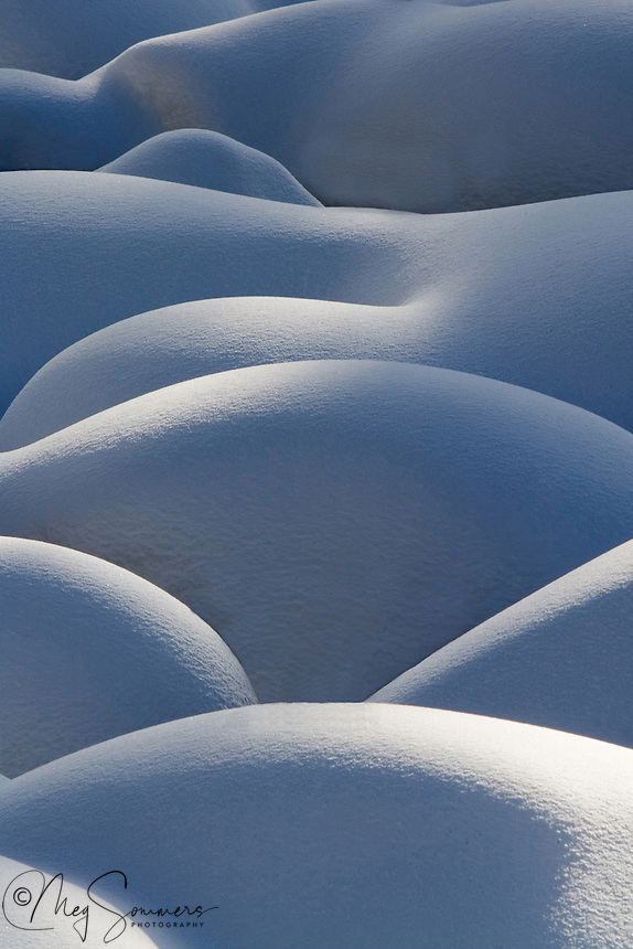 "Snow pillows form on Soda Butte Creek in the NE corner of Yellowstone during the deep winter months.  These ""pillows"" are really rocks in the stream bed covered with snow. It is the light that makes them really special :)"