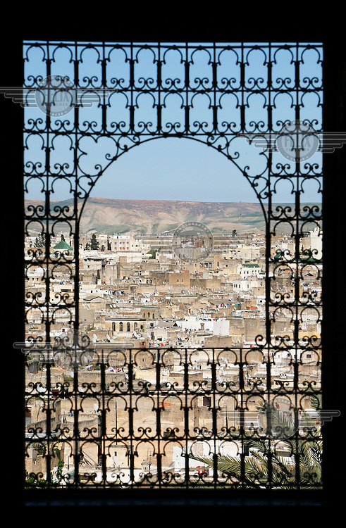 View of the medina through a window with metalwork in the Riyad Moqri. This Riyad was constructed in the beginning of the 20th Century by Driss Moqri. The palace is now home to an institute for traditional crafts in the construction sector. The medieval medina Fes el Bali is classified as a UNESCO World Heritage Site.