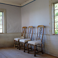 Three single chairs stand in a row against one wall of this dining room