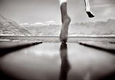 NEW ZEALAND, boy jumping into lake off pier, Lake Waikatipu, Queenstown (B&W)