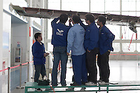 Chinese workers build an ARJ21 passenger plane at a factory of Shanghai Aircraft Manufacturing Company in Shanghai, China on November 12, 2009.