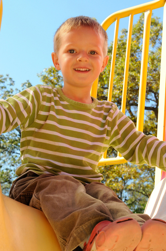 Sun shining brightly on a beautiful boy, sitting on top of a slide, in a playground