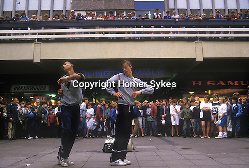 Break Dancing Stockport Lancashire. 1980s Britain. Crowds gather at shopping centre to watch two young men display their skills. Note the music comes from a so called Ghetto Blaster, a radio tape recorder player on floor half hidden.