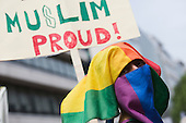 "29 June 2013, London, United Kingdom. Picture: A gay muslim stands in front of a poster of a gay muslim group. Pride London 2013 parade starts with the motto ""love (and marriage)""."
