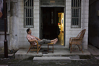 A Chinese man enjoys a quiet moment in the evening outside his home along the Grand Canal of China in Wuxi, Jiangsu province, in June, 2014.