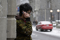 2006 Model Release Photo -<br /> 14 year old chinese teenager use a cellular phone outdoor, Old-Montreal during winter