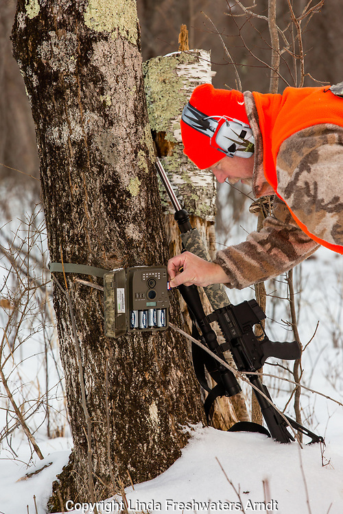 Wisconsin hunter checking trail camera