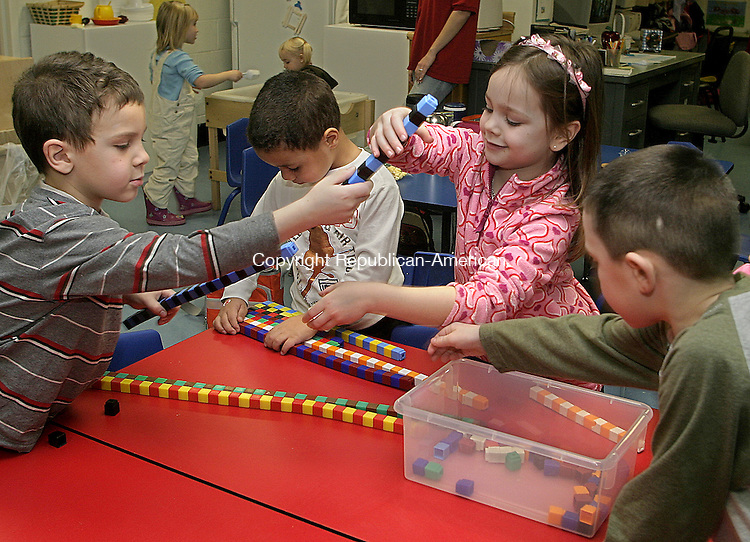 TORRINGTON, CT -11 JANUARY 2007 -011108DA01-Torrington YMCA All-Day Kindergarden students, from left, Trent Thomspon,5, Arron Bianer, 5, Cheyenne Harvey-Stoltz, 5, and Connor Tyrian, 6, works together connecting unifix cubes during a hands on pattern math unit Friday. The Torrington's YMCA and Catholic schools have the only All-Day Kindergarden programs in the city. The programs have gained a lot of support nationwide in the past several years as better preparing kids for later success. Torrington Public Schools are looking at implementing the programs at all five elementary schools sometime in the next few years.<br /> Darlene Douty/Republican-American