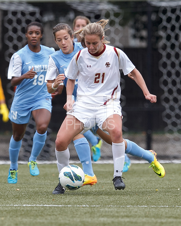 Boston College midfielder Kate McCarthy (21) controls the ball as University of North Carolina midfielder Paige Nielsen (24) pressures.  University of North Carolina (blue) defeated Boston College (white), 1-0, at Newton Campus Field, on October 13, 2013.