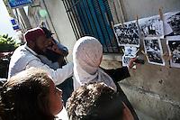 Tunisia, Tunisi, il dopo Rivoluzione. Alcune persone guardano delle foto appese in strada. Due uomini sorridono e una donna con il velo scatta una fotografia con il cellulare. <br /> TUNISIA after spring revolution