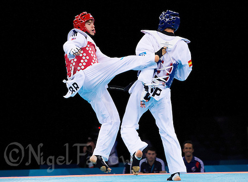 04 DEC 2011 - LONDON, GBR - Aaron Cook (GBR) (on left, in red) strikes Nicolas Garcia (ESP) (on right, in blue) during their men's -80kg category semi final contest at the London International Taekwondo Invitational and 2012 Olympic Games test event at the ExCel Exhibition Centre in London, Great Britain .(PHOTO (C) NIGEL FARROW)