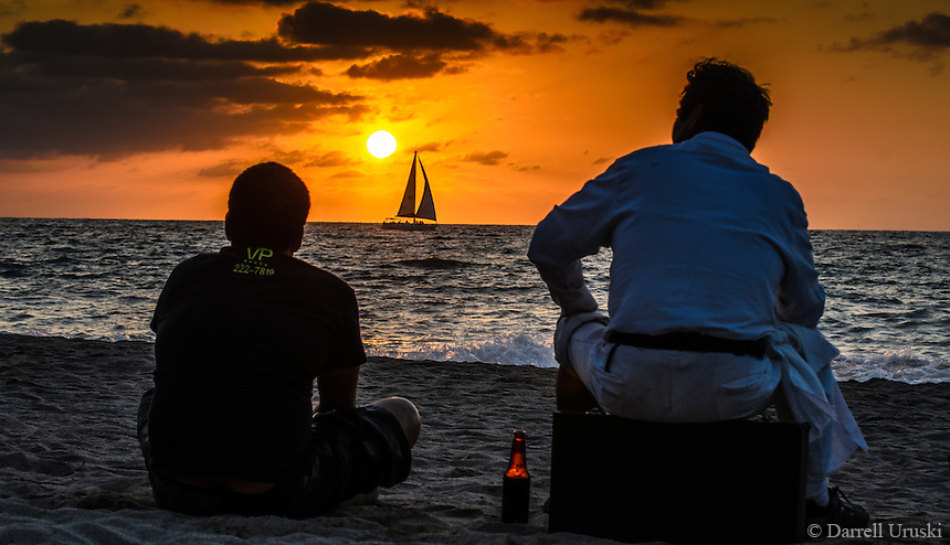 Fine Art Print, Photography. Sunset scene of beach vendors enjoying their evening beer as a sail boat passes in front of the setting sun. Bandaras Bay, Puerto Vallarta, Mexico.