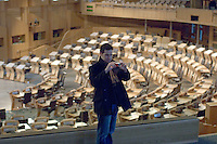 Visitor taking photos in the debating chamber at the new Scottish Parliament building at Holyrood, Edinburgh.  Designed by Spanish architect, Enric Miralles.