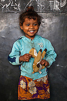 Sahnaz, 3, poses for a portrait with a soft toy in the Guria Non-Formal Education center in the middle of the Shivdaspur red light district, Varanasi, Uttar Pradesh, India on 20 November 2013. Guria uses the soft toys as a form of therapy for the children of the women in prostitution and also use it as signals of the children's emotional wellbeing.