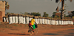 In northern Uganda,  bicycle travel is an increasingly important means for hauling water, crops and family members.   in the photo, a woman carries her sun past bags of charcoal for sale along the roadside.  After years of brutal insurgency by Joseph Kony's  Lords Resistance Army (LRA), the region is now peaceful, and recovering.
