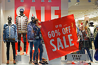Staff at River Island fix 60% sale signs to the shop window in Oxford Street, in the city centre of Swansea, Wales, UK. Sunday 24 December 2017