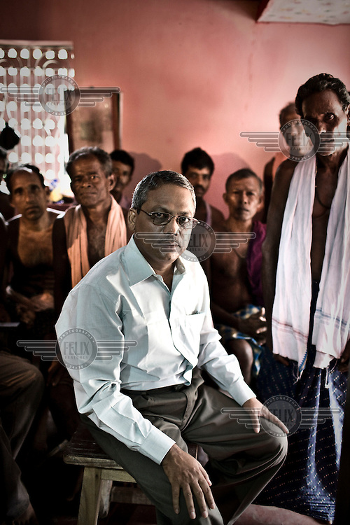 """Anti-Posco leader and president of Posco Pratirodha Sangram Samiti, Mr. Abhaya Sahoo, with local villagers in Nuagaon village. Sahoo has been spearheading the anti-Posco movement in Dhinkia panchyat for three years. In October 2008 he was arrested, and spent 10 months in jail, until he was finally released on conditional bail by Orissa High Court. All the residents of this village would be displaced if plans for the new steel works are allowed to proceed. South Korean steel giant Posco continues to face stiff public resistance in Orissa's Jagatsinghpur district where the company is setting up India's biggest direct foreign investment project of a 12 million tonne steel plant, at the cost of USD 12 Billion. Villagers have formed an agitating group, """"Posco Pratirdh Sangram Samiti"""" to oppose the construction of the Posco development, which will displace thousands of people and make agricultural land untenable."""