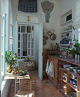 Marble work surfaces, a tiled floor and open shelves displaying antique china are combined in a kitchen of great charm and character
