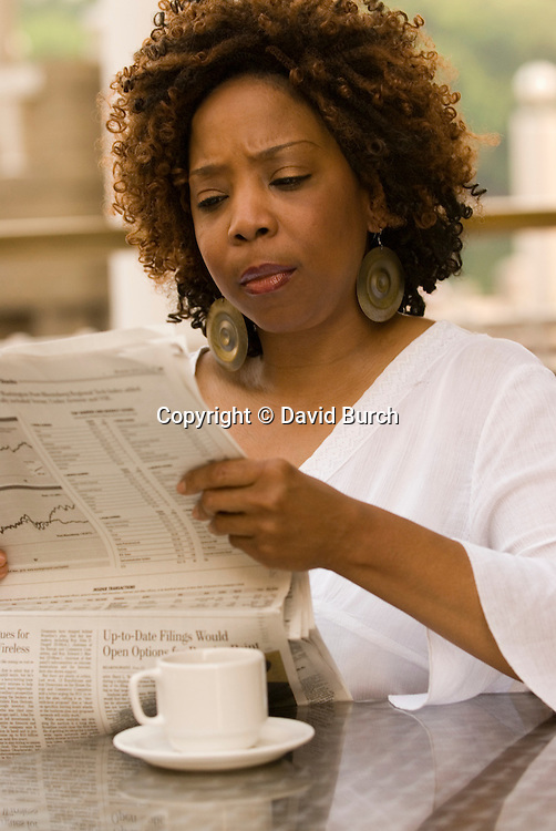African American woman reading newspaper, pensive