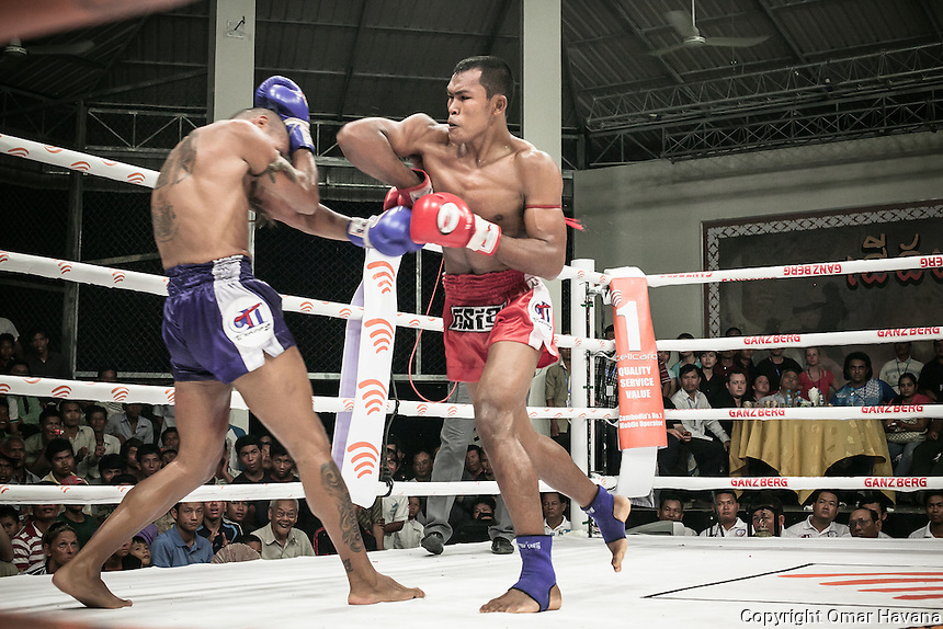 SIEM REAP, CAMBODIA. Vorn Viva, ISKA (International Sport Karate Association) Middleweight world champion, elbows his opponent, the Colombian Eddie Vendetta, during a fight in the Siem Reap arena in Cambodia. On August 2008, Cambodian boxers Vorn Viva and Meas Chantha won the ISKA Middleweight and Welterweight world titles in Phnom Penh; it was the first time a Cambodian had held a kickboxing world title. Pradal Serey or Kun Khmer -free fighting- is an unarmed martial art from Cambodia. Compared to other forms of Southeast Asian kickboxing, Kun Khmer emphasises more elusive and shifty fighting stances. The Cambodian style tends to utilise more elbows than that of other regions. Evidence shows that a style resembling pradal serey existed in the 9th century, leading the Khmer to believe all Southeast Asian forms of kickboxing started with the early Mon-Khmer people. They maintain that Pradal Serey has influenced much of the basis of Muay Thai. During the Khmer Rouge genocide, traditional martial arts were banned and many boxers were executed or worked to death, which nearly caused the death of pradal serey. Nowadays, Kun Khmer is making a strong comeback in Cambodia, with fighters attempting to market their style of boxing at the same caliber of Muay Thai. Photography: ©Omar Havana