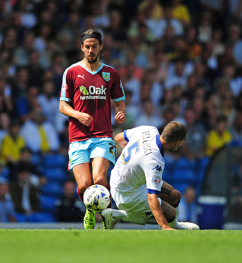 Burnley's George Boyd skips the challenge of Leeds United's Giuseppe Bellusci<br /> <br /> Photographer Chris Vaughan/CameraSport<br /> <br /> Football - The Football League Sky Bet Championship - Leeds United  v Burnley - Saturday 8th August 2015 - Elland Road - Beeston - Leeds<br /> <br /> &copy; CameraSport - 43 Linden Ave. Countesthorpe. Leicester. England. LE8 5PG - Tel: +44 (0) 116 277 4147 - admin@camerasport.com - www.camerasport.com
