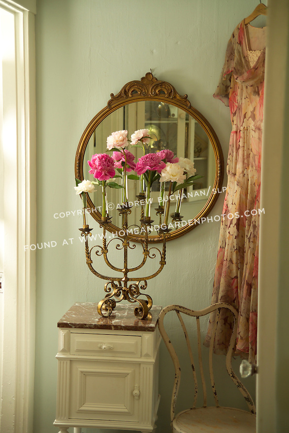 Antique and collectable stores offer all manner of everyday objects that can find new life as vases and stem holders for flowers.  Even an antique candleabra and reclaimed test tubes find new life as bud vases for these peony blooms resting on a side table in this quiet hallway.