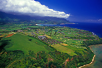 An aerial view of Princeville, Kauai, with a bank of clouds against the bright blue sky in the distance