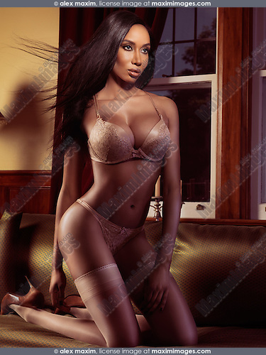 Glamorous african american woman in lingerie and stockings kneeling on a sofa in front of a window