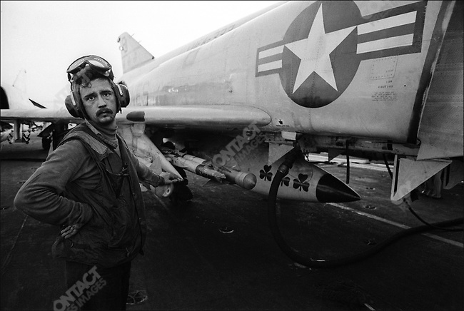 A US Navy crewman in charge of getting planes ready for launch, with his F-4 Phantom jet, on the USS AMERICA aircraft carrier operating off the coast of South Vietnam, August 1972.
