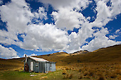 Cumulus clouds drift above a shepherds hut in the Upper Nevis valley, Central Otago District, Otago, South Island, New Zealand.