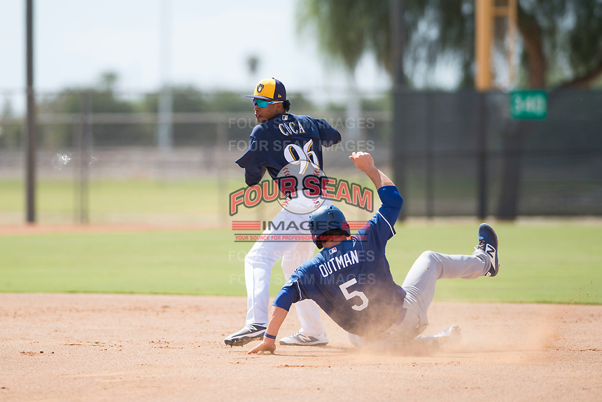 Milwaukee Brewers second baseman Yeison Coca (96) prepares to make a throw to first base on a double play attempt as James Outman (5) slides into second base during an Instructional League game against the Los Angeles Dodgers at Maryvale Baseball Park on September 24, 2018 in Phoenix, Arizona. (Zachary Lucy/Four Seam Images)