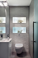 A textured wall of raised, narrow tiles at varying heights frames illuminated boxes of coral in this bathroom