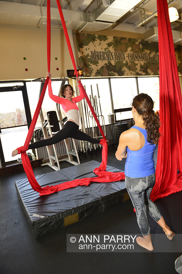 JOY ROBINSON, in blue top, has aerial silks lesson from Aerial Arts instructor MARYANN STEVENS, in pink top, at The Fitness Loft, Manhasset, New York, USA, on March 31, 2014.