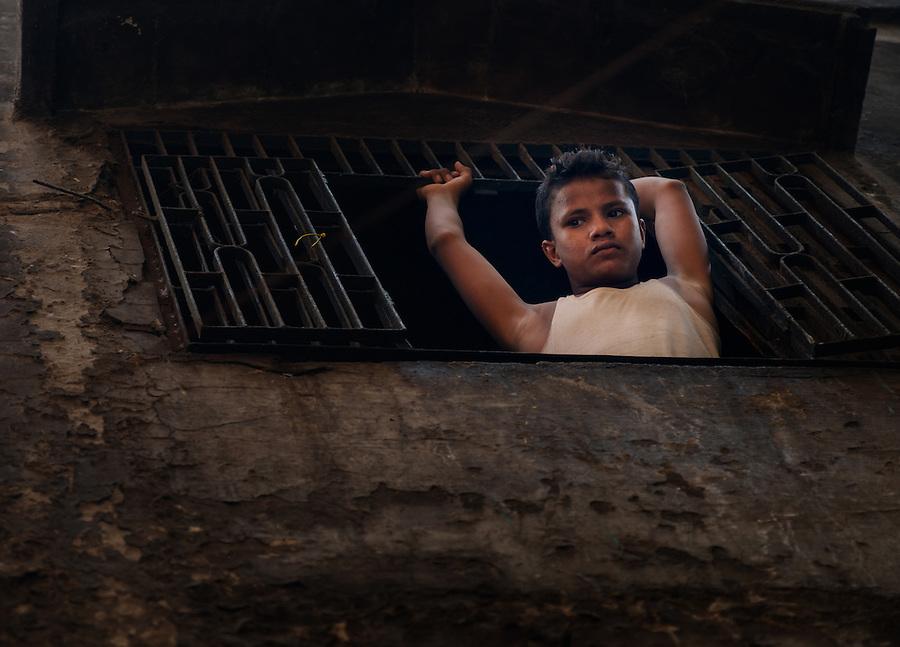 VARANASI, INDIA - CIRCA NOVEMBER 2016: Portrait of a young boy looking through a windown in Varanasi.