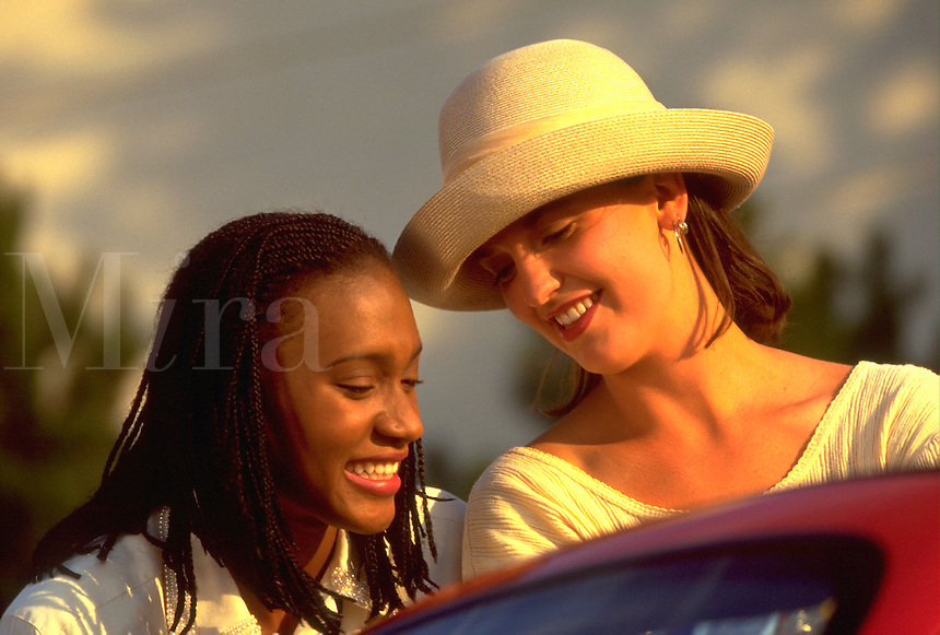 African-American Woman and Hispanic Woman (wearing hat) chatting together; friends, friendship, Black, Latina women. Kim Mayes, Kimberly S. Garcia.