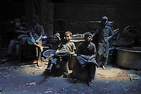 Children take a rest during the working day at a silver cooking pot factory. The child labourers earn about 200 taka per week and they work about 10 hours a day.