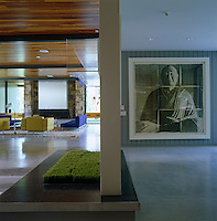 A photograph of a Buddha hangs in the entrance hall while on the other side of the partition wall is a view of the modern living room with a wood clad ceiling
