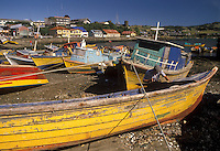 AJ2094, boats, Chile, Chiloe Island, Colorful fishing boats beached at low tide in the harbor in Ancud on the Pacific Ocean on Chiloe Island in Chile. Local man repairing yellow fishing boat on the beach.