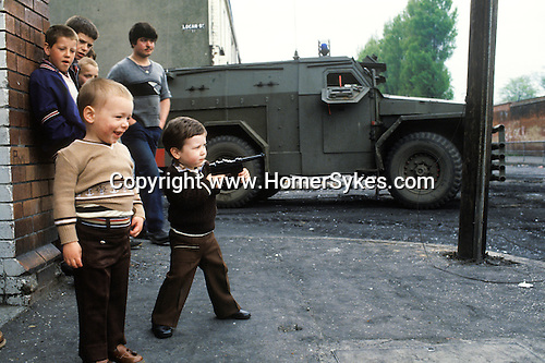 Ireland The Troubles. Belfast young boy with toy gun. British soldier patrols street behind. Downtown urban shopping street Belfast. 1980s. The vechicle, is an armoured personnel carrier,  a  Humber 1 Ton (Pig).<br /> <br /> Danny Devine plays with toy gun, he lived here in Beechmount Avenue &ldquo;RPG Avenue&rdquo;, named after the rocket-propelled grenade launchers used by the IRA.