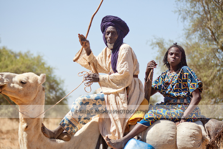 "In West Africa, certain villages have markets that ""assemble"" at regular intervals, such as weekly or every three days.  People from villages around the region come on market day to buy and sell food, livestock, and other goods and services.  In this photo, a Tuareg man and his wife come to the village market of Bourro in northern Burkina Faso by camel."