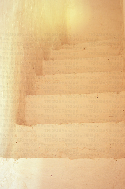Flight of stone steps painted white leading to white passage with brighter light