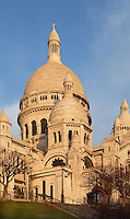 PARIS, FRANCE - JANUARY 20: A low angle view of  Sacré-Coeur Basilica, on January 20, 2009, in Montmartre, Paris, France. Sacré-Coeur Basilica, built 1884-1914, was designed by Paul Abadie. Constructed in white travertine on the top of the Butte Montmartre, the Romano-Byzantine style SacrÈ-Coeur was designed as a monument to those who died in the Paris Commune during the Franco-Prussian War, 1870-71. Its clustered white domes are seen against a clear sky on a winter morning. (Photo by Manuel Cohen)
