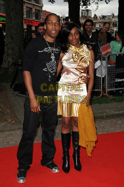 """LEMAR OBIKA & GUEST .Attending the UK Gala Premiere of """"Hancock"""" held at the Vue West End, Leicester Square, London, England..June 18th 2008.full length ed hardy t-shirt black gold cream silk satin dress jeans denim.CAP/CAS.©Bob Cass/Capital Pictures."""