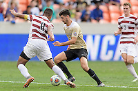 Houston, TX - Friday December 11, 2016: Jon Bakero (7) of the Wake Forest Demon Deacons attempts to dribble the ball around Brian Nana-Sinkam (8) of the Stanford Cardinal at the NCAA Men's Soccer Finals at BBVA Compass Stadium in Houston Texas.