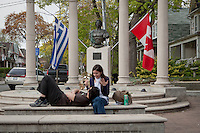 A couple hangs out in a small park at Logan and Danforth avenue in Toronto Greektown April 24, 2010. Greektown, also known as Greektown on the Danforth, or more simply, The Danforth, was one of the major settlement areas of early Greek immigrants to Toronto now filled with number of Greek restaurants and stores.