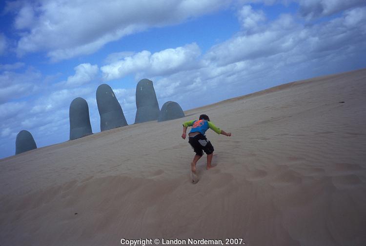 PUNTA DEL ESTE, URUGUAY- MARCH 2005:  People enjoy the beach and a burried sculpture of a hand in Punta del Este, Uruguay.  (photo by Landon Nordeman)